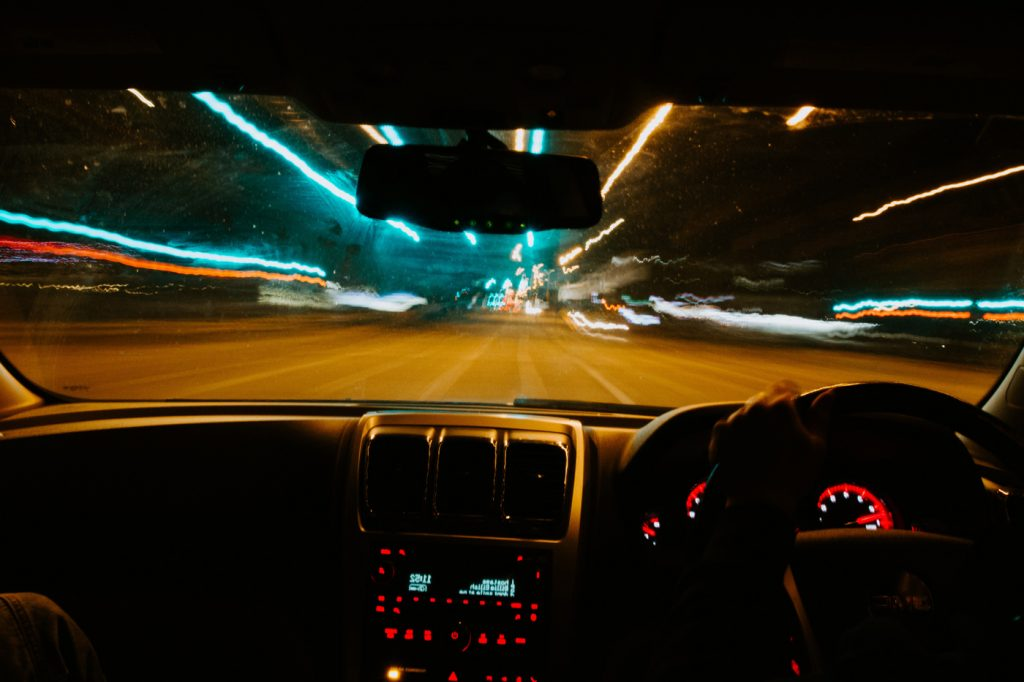 A car dashboard with blurred street lights indicating the drier is intoxicated.