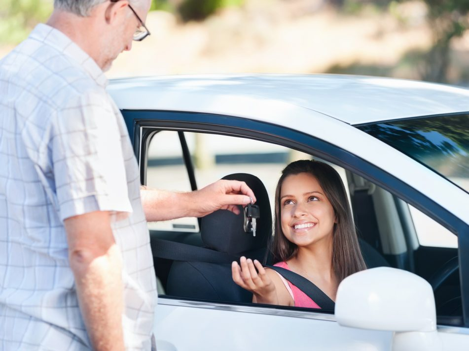 A new driver sitting in their first car being handed the keys by their dad