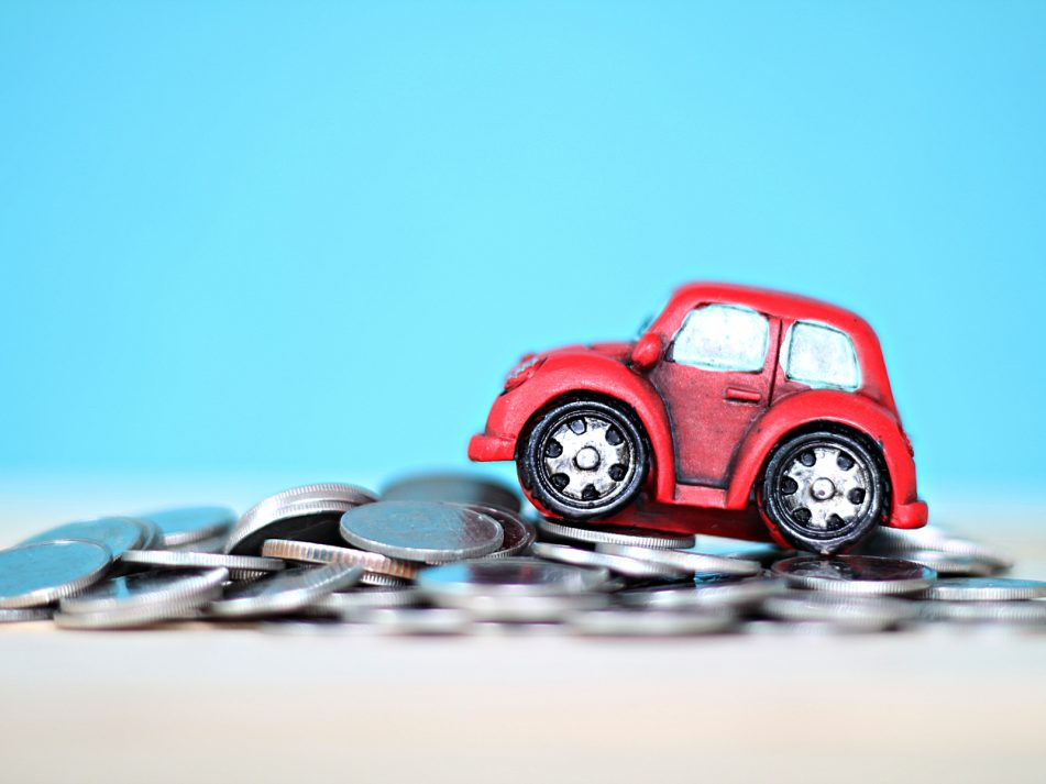 A model of a car placed on-top of a pile of coins against a blue background