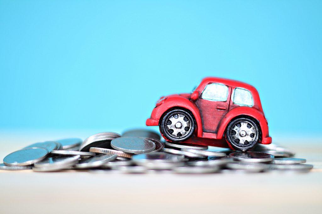 A model car put on a pile of coins against a plain blue background.