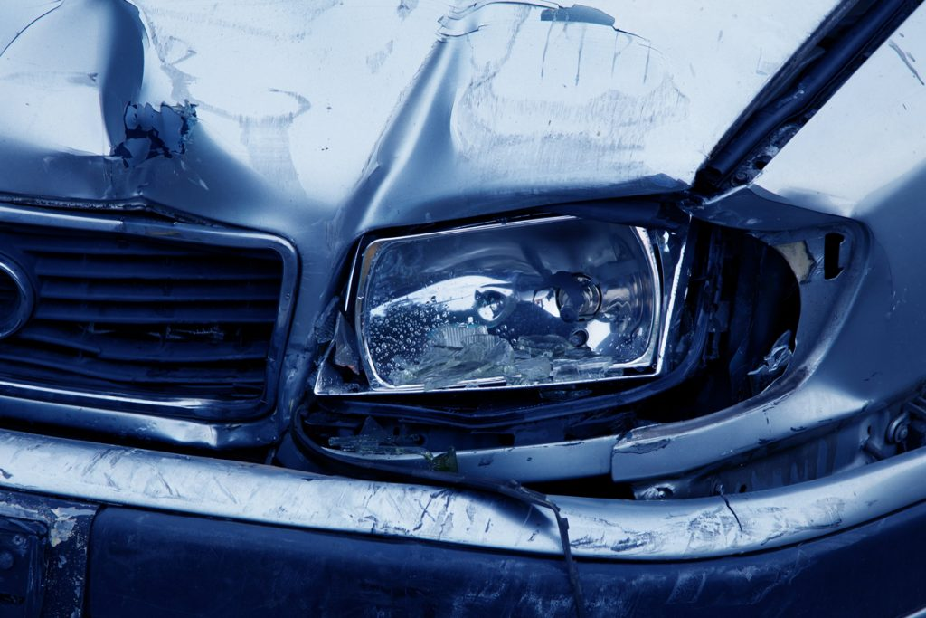 A broken headlight with crumpled metal around it on a silver car that has crashed