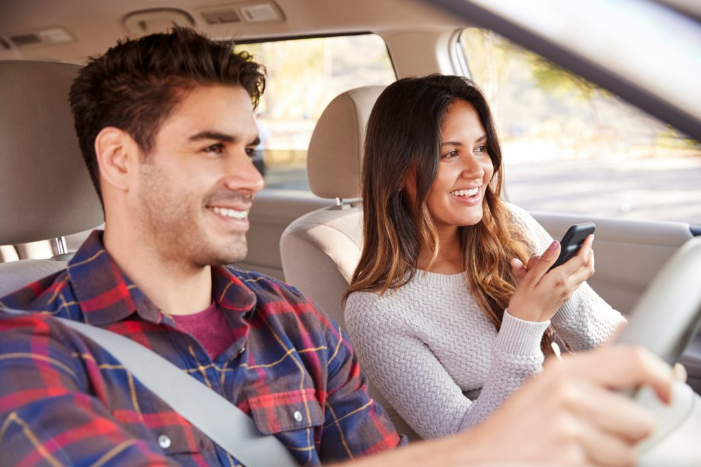 A man driving with a woman sitting in the passenger seat holding a phone up to speak