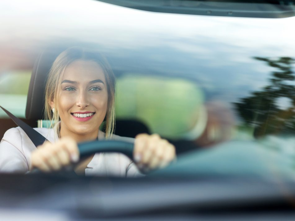 A young driver smiling as she driver her car