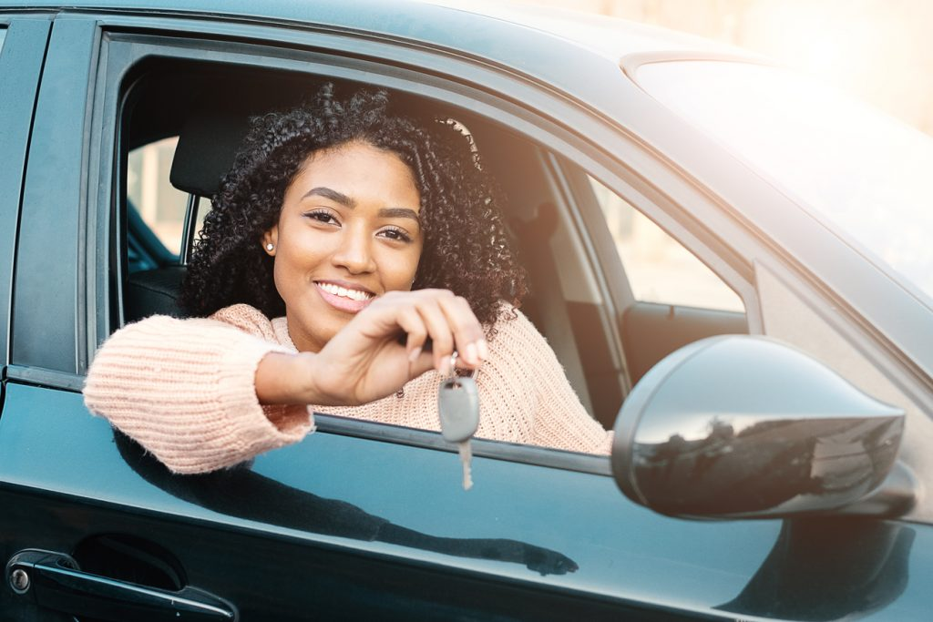 A young woman sitting in her car holding the key out of the window smiling
