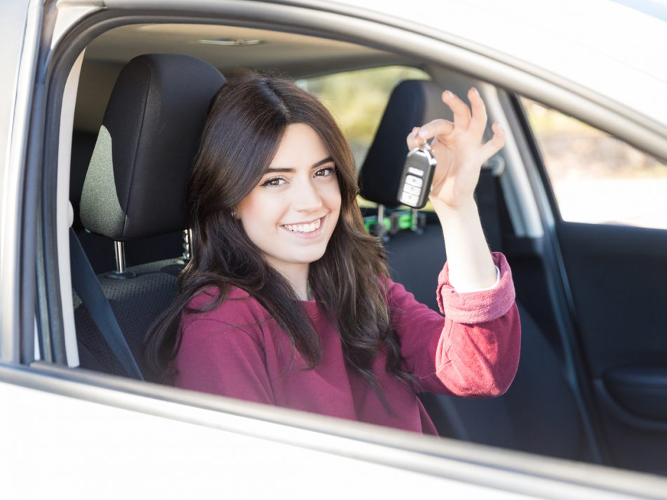 A young female driver holding up the keys to a car whilst sitting in the driver's seat