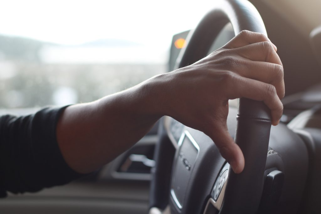 A young persons hand on a steer wheel as they drive a car