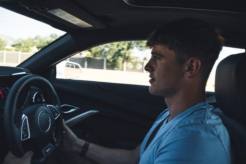 A young man driving a new car