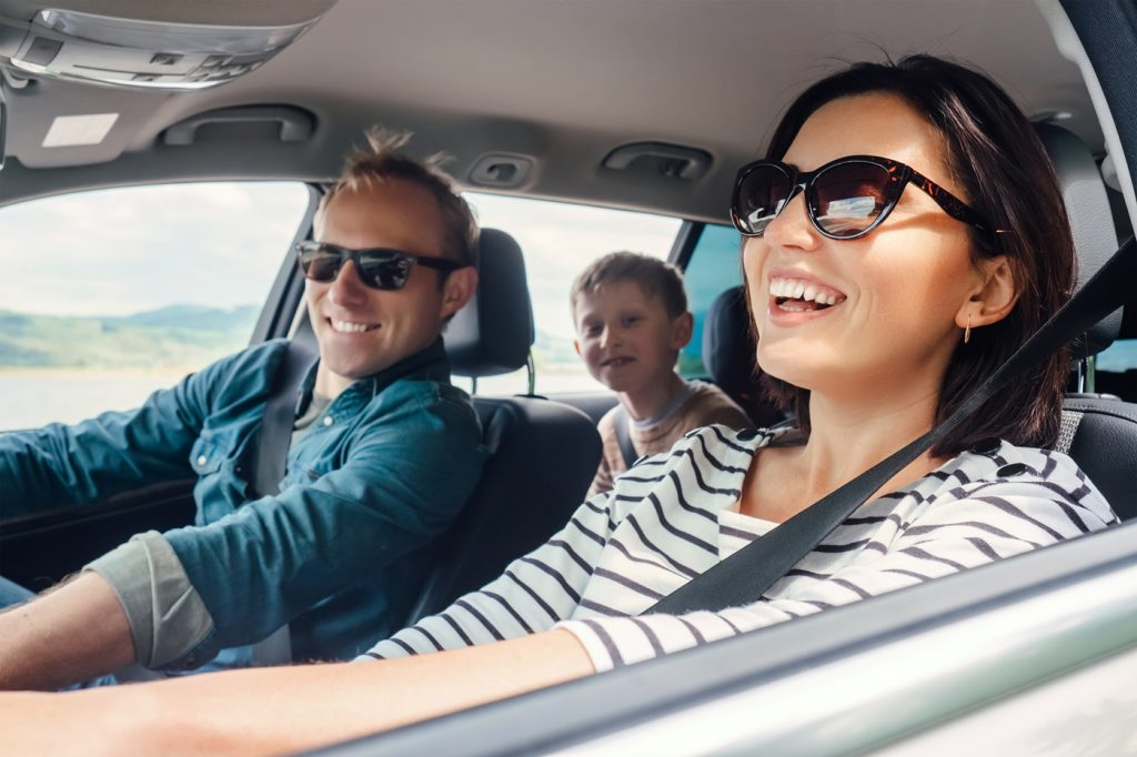 A family smiling and laughing during a car journey