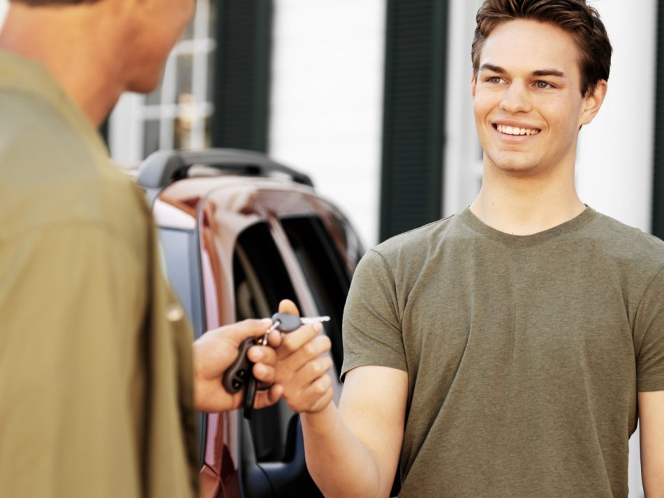 A father handing the keys of a new car over to his son