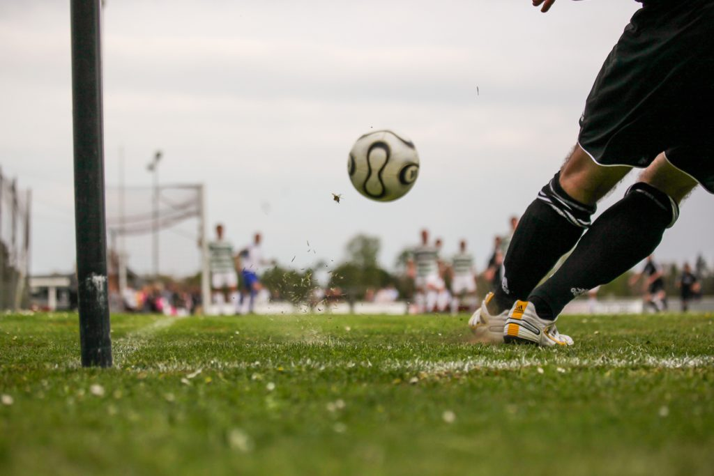 A professional footballer taking a corner kick during a match