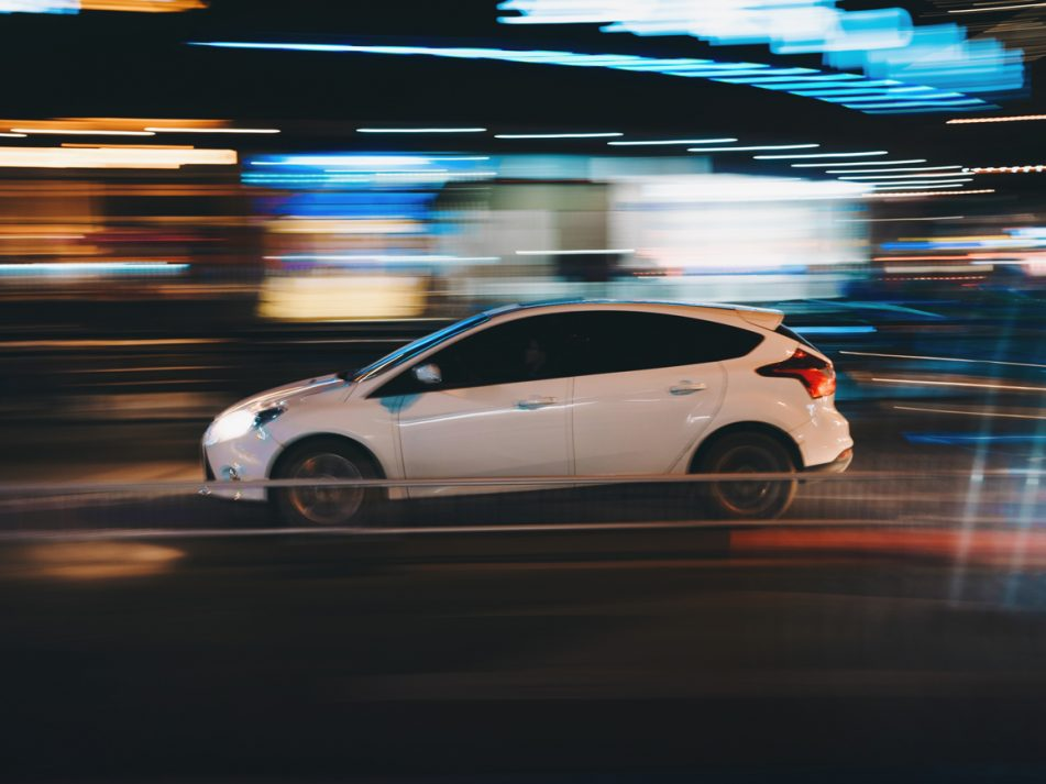 A white car driving through a brightly lit street at night