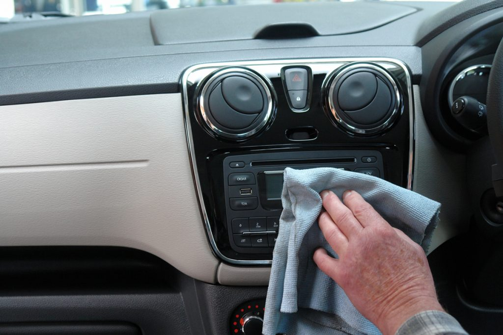 A person cleaning the dashboard of their car with a cloth