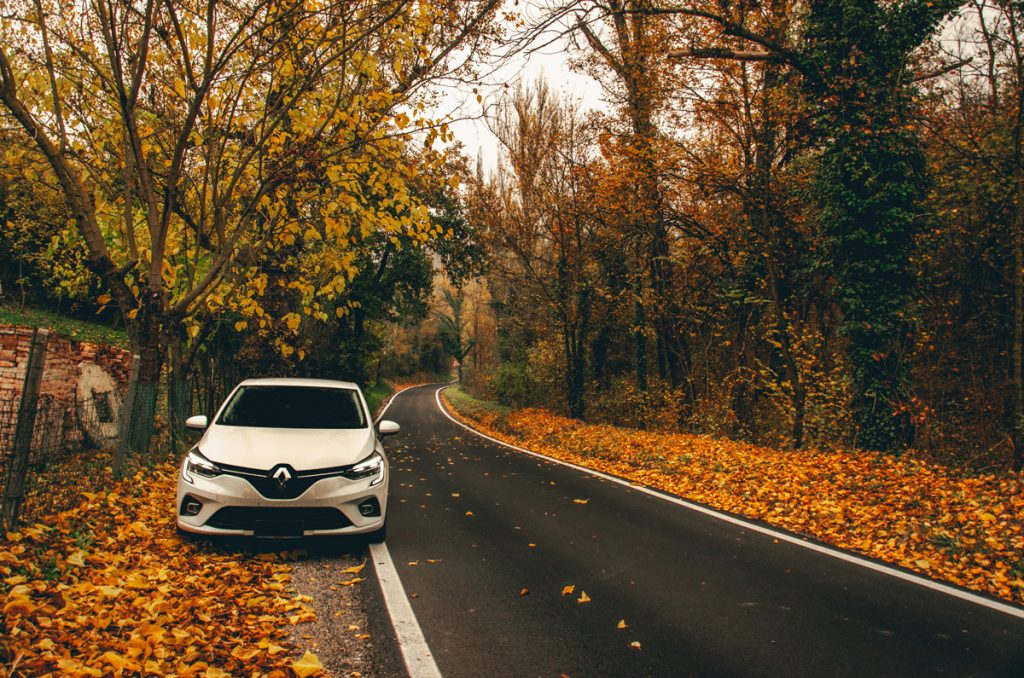 A white Renault Clio parked at the side of a country road with brown leaves lining the sides of the road