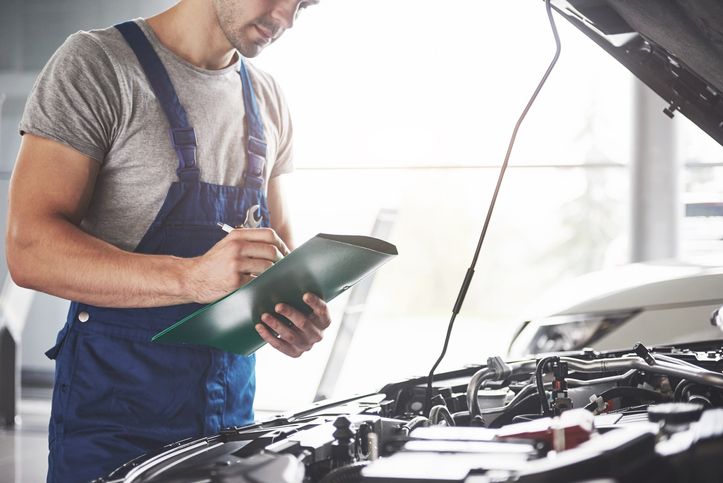A mechanic inspecting the engine of a car writing on a clip board
