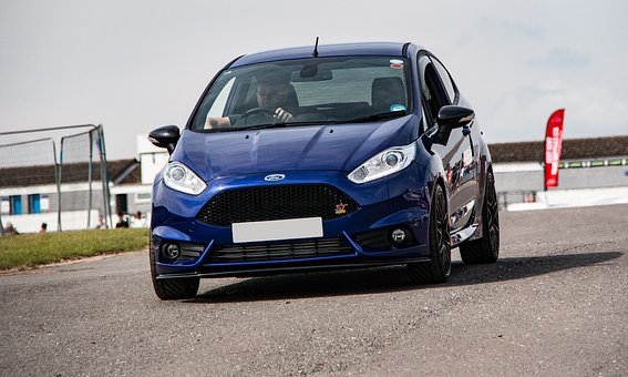 A blue ford fiesta driving along a tarmac area