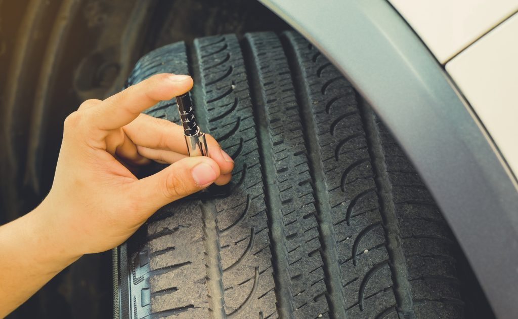 A person using a tool to check the depth of the tread on their car tyre