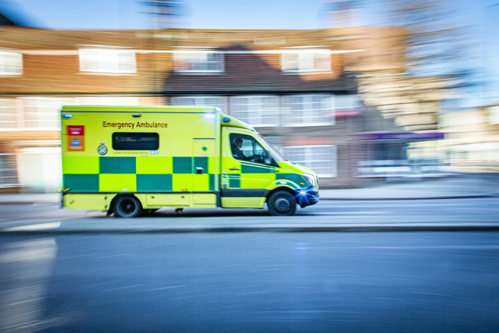 An ambulance driving along a high street at high speed with its sirens on