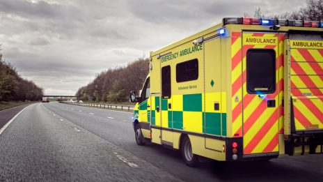 An ambulance passing in the fast lane of a dual carriage way with its lights on