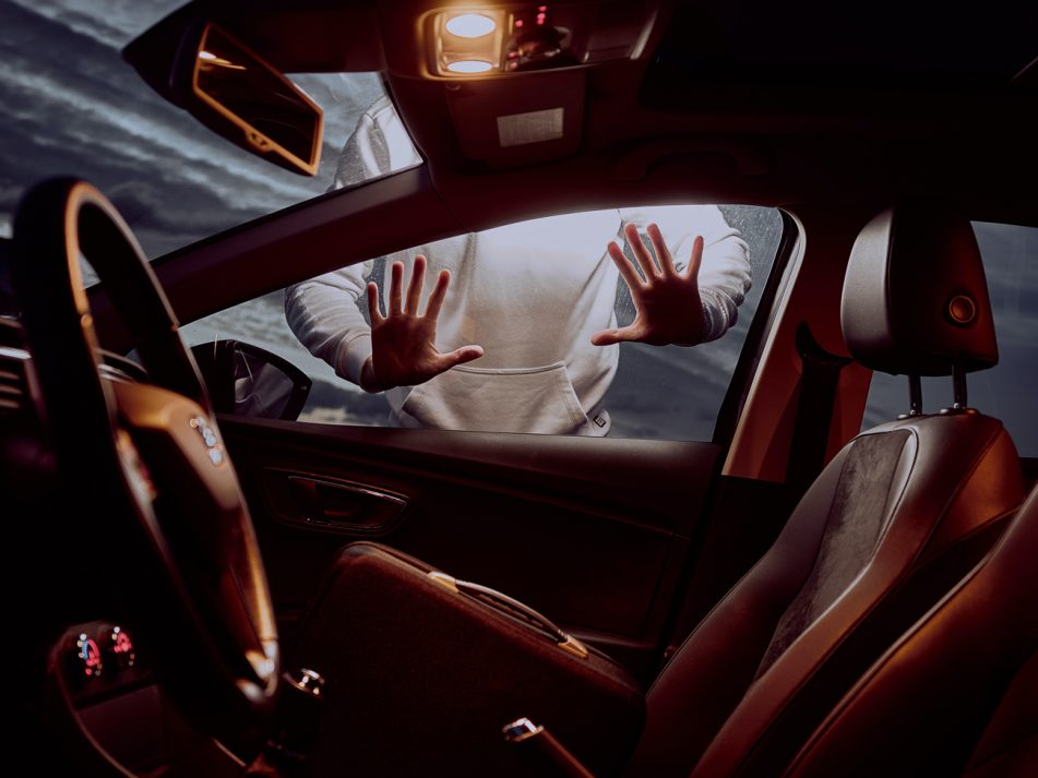 A thief putting their hands onto the window of a car looking to steal it