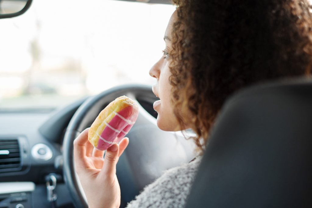 A woman eating a donut while driving