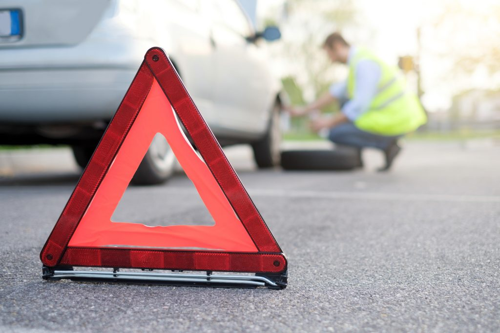 An emergency triangle set-up in-front of a car with a man in a high-vis vest changing the wheel