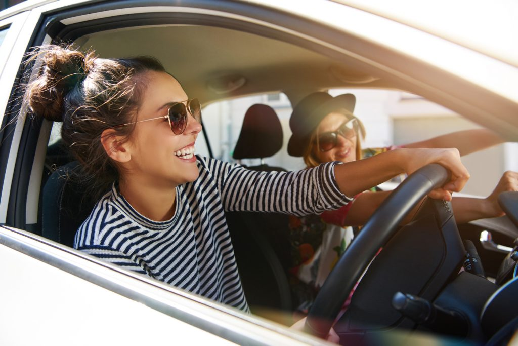 Two girls in a car driving with their sunglasses on with the sun behind