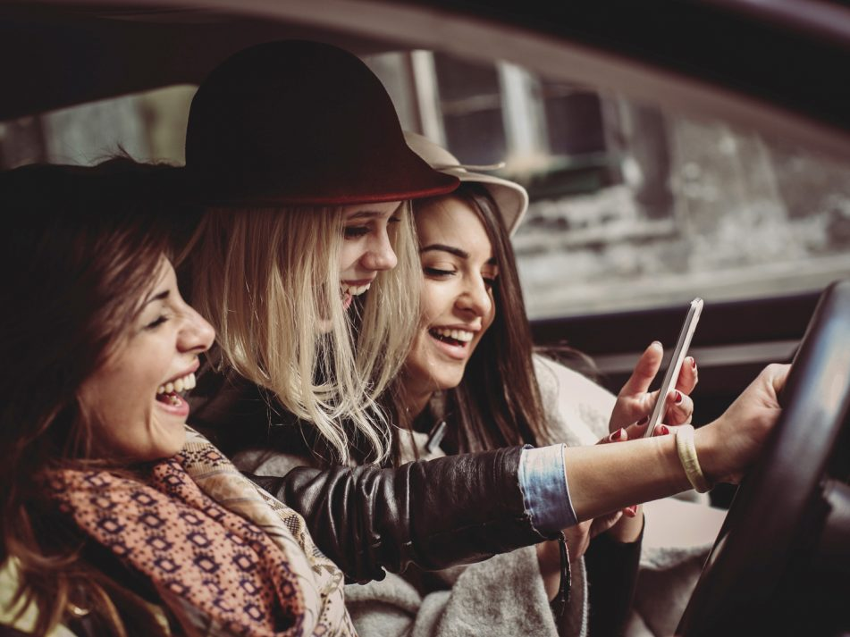 A woman driving with her two friends laughing and distracting her