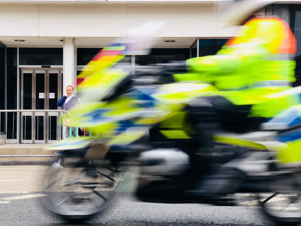 A police motorbike passing in-front of a city building at speed.