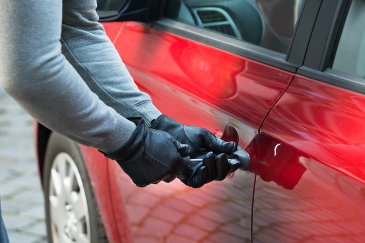 Close-up photo of a thief using a tool to break into a car