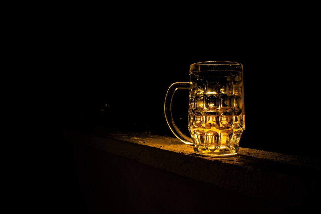 An empty beer glass in a dark room