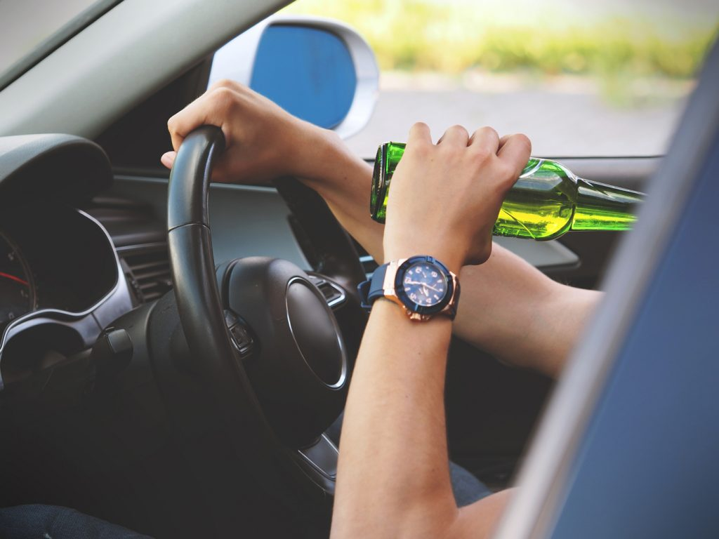 A person drinking from a beer bottle whilst driving