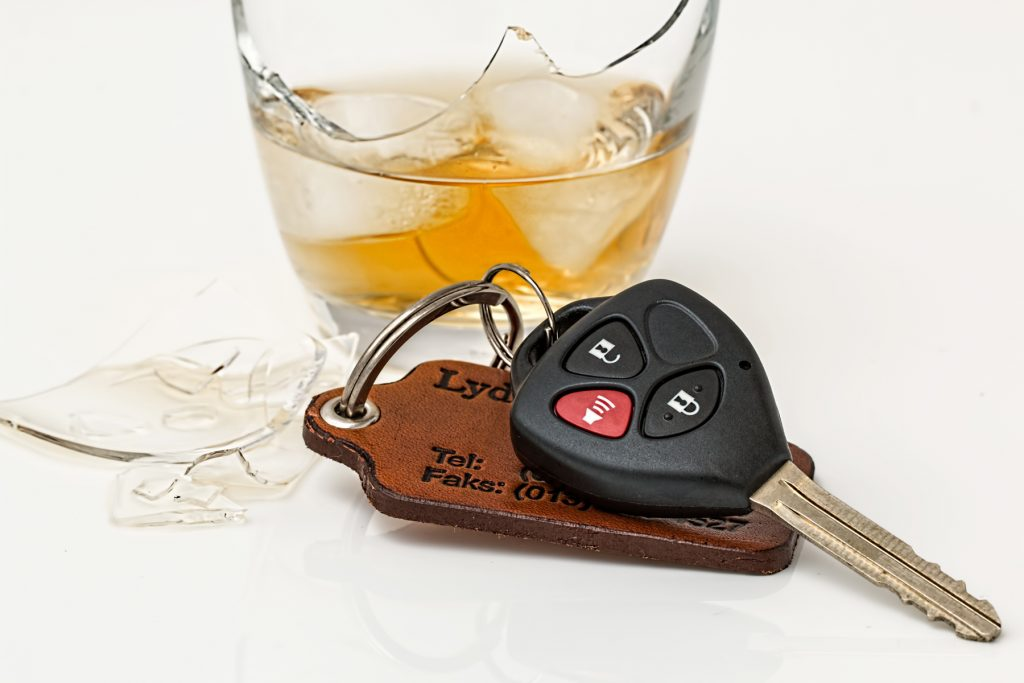 A pair of car keys next to a broken glass containing whiskey