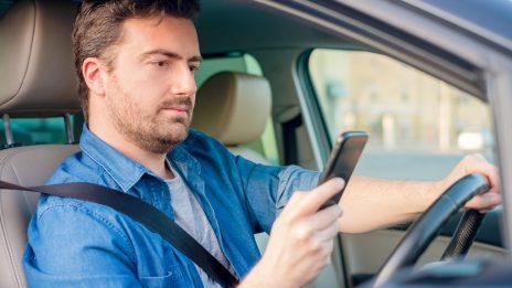 A driver using his phone while driving a car