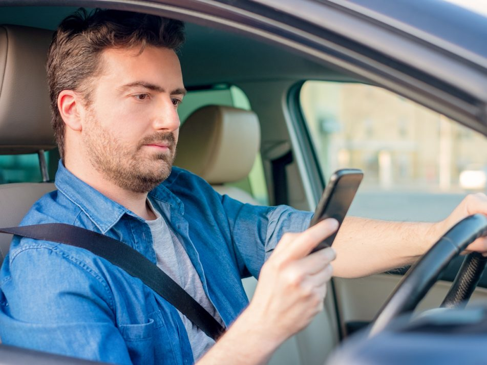 A driver using his phone while driving a car