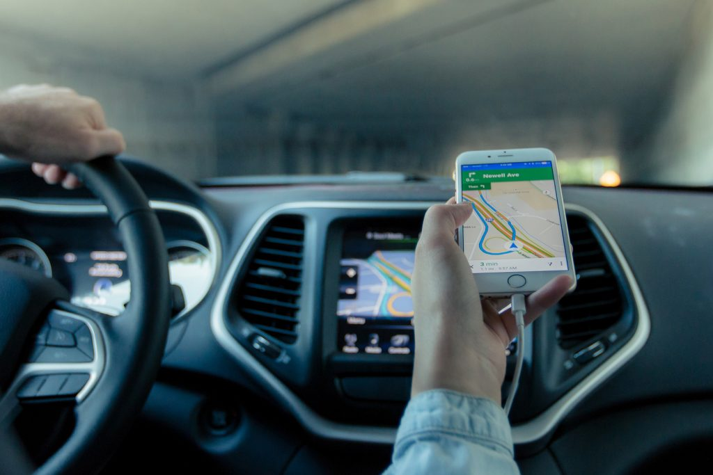 A passenger using their mobile phone for navigation to show the driver directions
