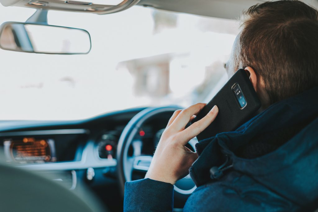 A man holding a mobile phone up to his ear to talk whilst driving a car