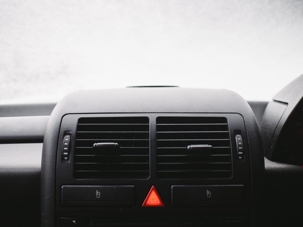 A red triangle button to turn the hazard lights on in the centre of a car dashboard