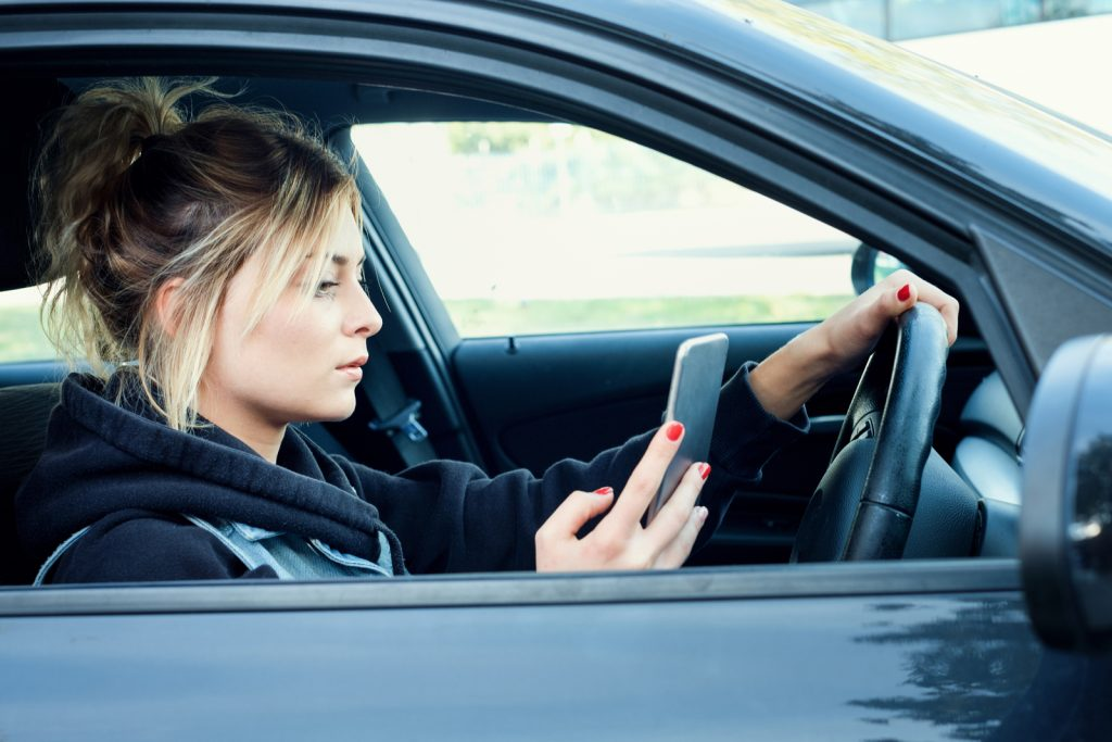 A young woman using her phone with one hand whilst driving