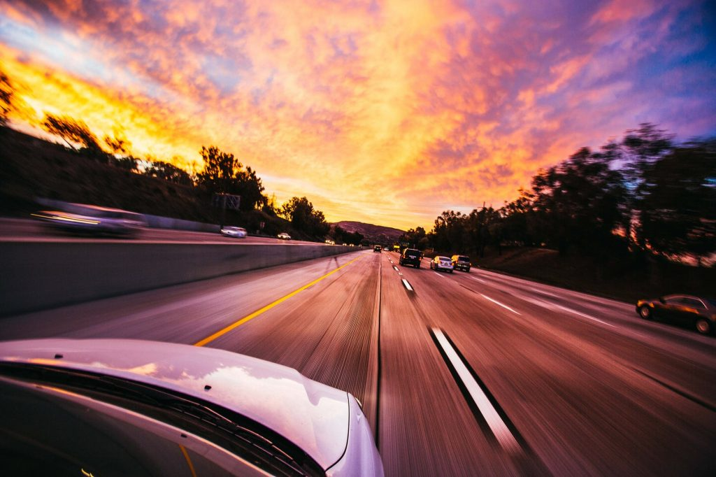 A car speeding along a motorway at sunset
