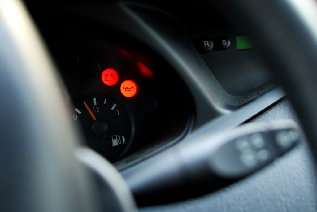 A red and an orange warning light lit up on a car dashboard