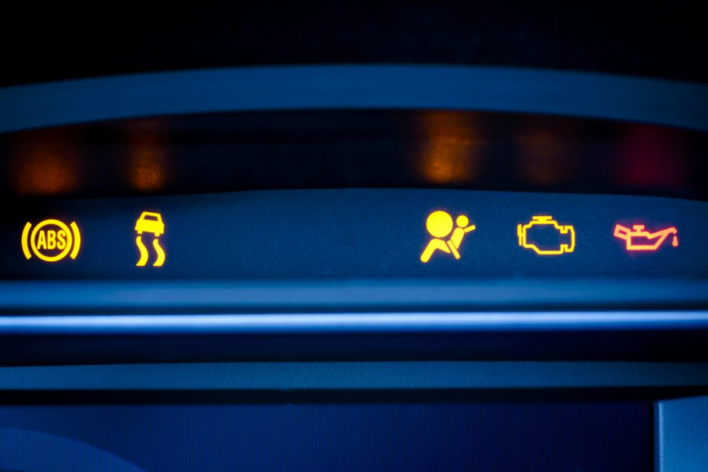 Various warning lights lit up on a dashboard