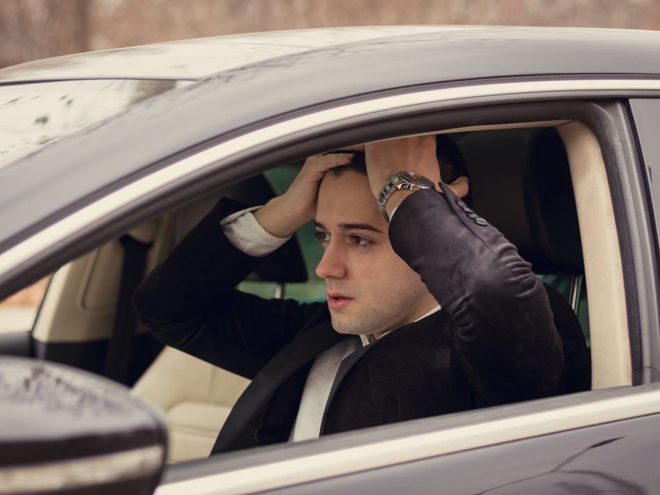 A man holding his hands on his head over being caught drink driving