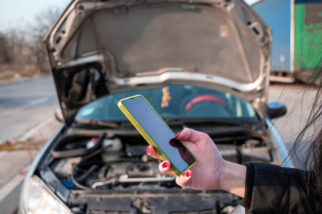 A person standing in-front of a broken down car using their mobile phone to call for assistance on the hard shoulder of a motorway