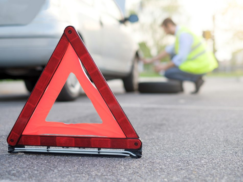 An emergency triangle placed behind a broken down car on a motorway