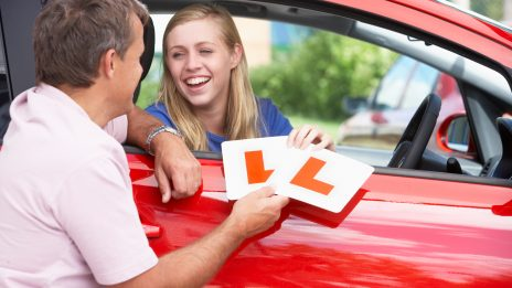 A dad handing L plates to his daughter that is sitting in a car