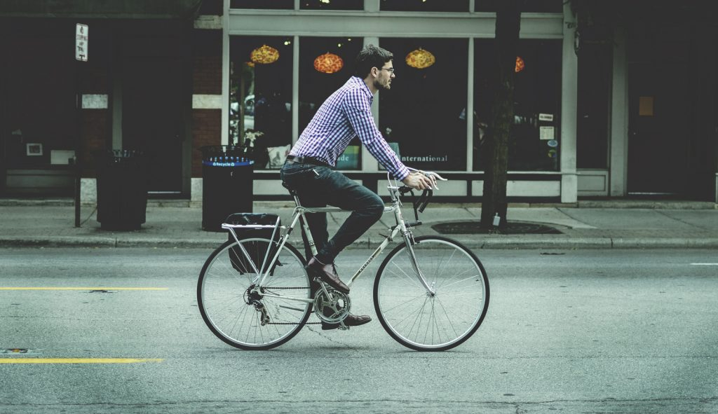 A commuter cycling to work on a city street