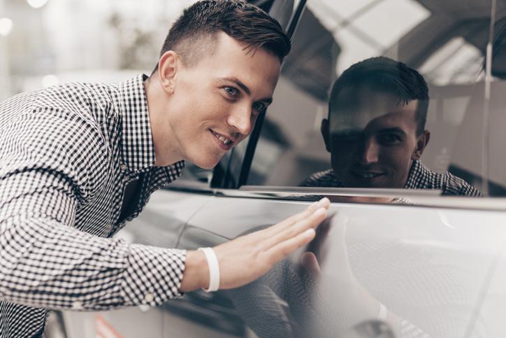 Young man buying car at automobile dealership